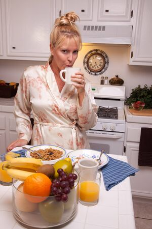 house robes: Attractive Woman In Kitchen with Fruit, Coffee, Orange Juice and Breakfast Bowls. Stock Photo