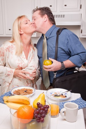 twenty two: Businessman Ready for Work Kisses Wife In Kitchen.