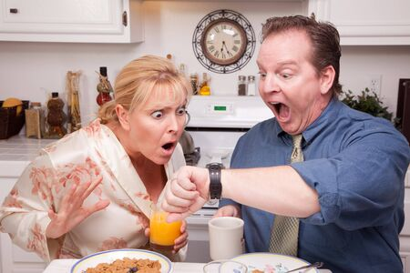 Late for Work Stressed Couple Checking Time in Kitchen. photo
