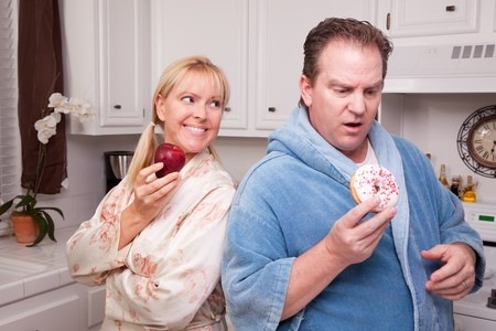 Couple in Kitchen Eating Doughnut and Coffee or Healthy Fruit. photo