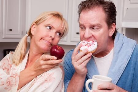 convincing: Couple in Kitchen Eating Doughnut and Coffee or Healthy Fruit. Stock Photo