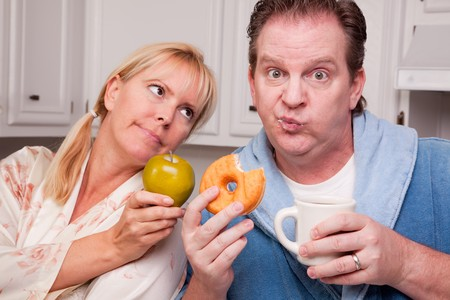 Couple in Kitchen Eating Doughnut and Coffee or Healthy Fruit. Stock Photo