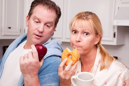 alternative living: Couple in Kitchen Eating Doughnut and Coffee or Healthy Fruit. Stock Photo