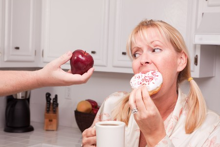 Couple in Kitchen Eating Donut and Coffee or Healthy Fruit. Stock Photo - 4388442