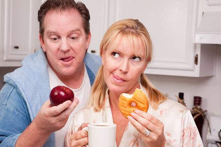 Couple in Kitchen Eating Donut and Coffee or Healthy Fruit. Stock Photo - 4391914
