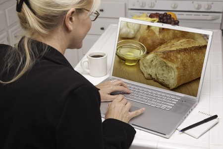 Woman In Kitchen Using Laptop to Research Cooking and Recipes. Screen can be easily used for your own message or picture. Picture on screen is my copyright as well. photo