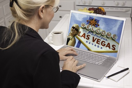 Woman In Kitchen Using Laptop to Research A Las Vegas Trip. Screen can be easily used for your own message or picture. Picture on screen is my copyright as well. Stock Photo