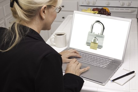 Woman In Kitchen Using Laptop with High Security Level. Screen can be easily used for your own message or picture. Picture on screen is my copyright as well. photo