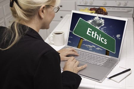 ethics and morals: Woman In Kitchen Using Laptop with Ethics Road Sign on Screen. Screen can be easily used for your own message or picture. Picture on screen is my copyright as well.