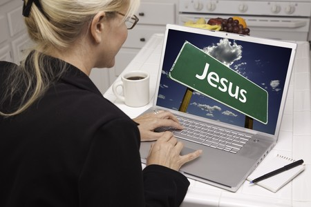 Woman In Kitchen Using Laptop with Jesus Road Sign on Screen. Screen can be easily used for your own message or picture. Picture on screen is my copyright as well. photo