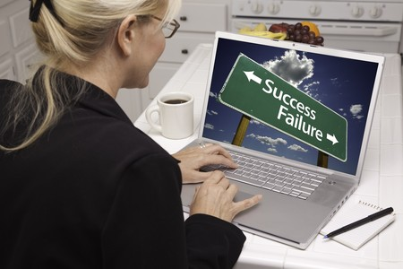 Woman In Kitchen Using Laptop with Success or Failure Road Sign on Screen. Screen can be easily used for your own message or picture. Picture on screen is my copyright as well. photo