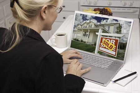 노트북을 사용 하여 부동산을 연구하는 부엌에서 여자. 화면을 쉽게 자신의 메시지 또는 그림에 사용할 수 있습니다. 화면의 그림도 내 저작권입니다.