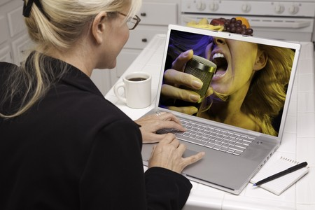 Woman In Kitchen Using Laptop for Music and Entertainment. Screen can be easily used for your own message or picture. Picture on screen is my copyright as well. photo