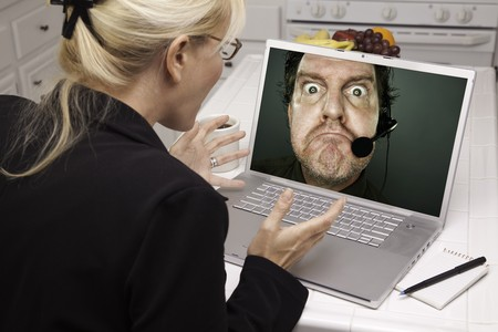 Shocked Woman In Kitchen Using Laptop with Grumpy Customer Support Man On Screen. Screen can be easily used for your own message or picture. Picture on screen is my copyright as well. photo