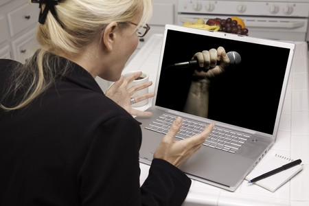 joining forces: Excited Woman In Kitchen Using Laptop for Freedom of Speech. Screen can be easily used for your own message or picture. Picture on screen is my copyright as well. Stock Photo