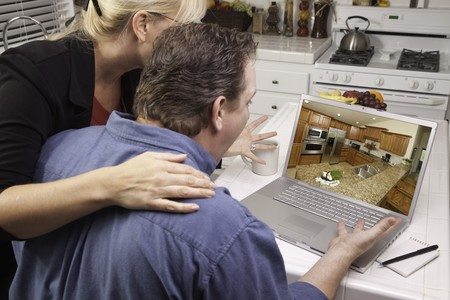 Couple In Kitchen Using Laptop to Research Home Improvement Ideas. Screen can be easily used for your own message or picture. Picture on screen is my copyright as well. photo