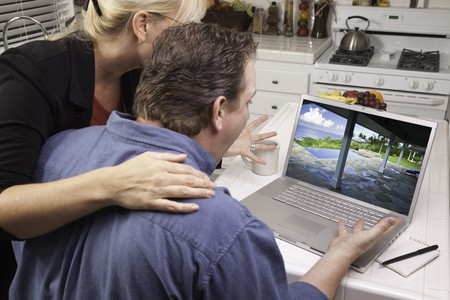 Couple In Kitchen Using Laptop to Research Travel and Vacations. Screen can be easily used for your own message or picture. Picture on screen is my copyright as well. photo