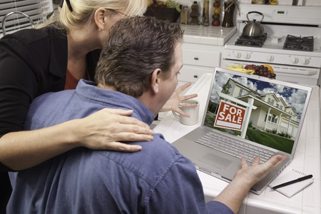 Couple In Kitchen Using Laptop to Research Real Estate. Screen can be easily used for your own message or picture. Picture on screen is my copyright as well. photo