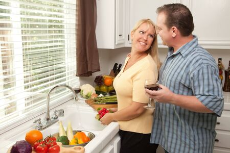Happy Couple Enjoying An Eveing Preparing Food in the Kitchen. photo