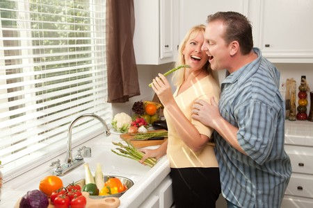 Happy Couple Enjoying An Eveing Preparing Food in the Kitchen. Stock Photo
