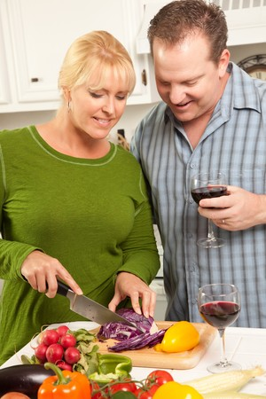 Happy Couple Enjoying An Evening Preparing Food in the Kitchen. photo