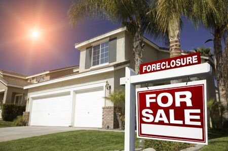 dispossession: Red Foreclosure For Sale Real Estate Sign in Front of House with Red Starburst in Sky.