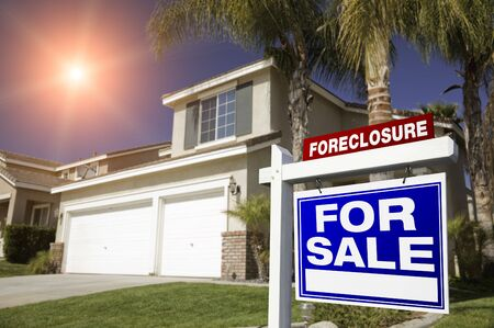 eviction: Blue Foreclosure For Sale Real Estate Sign in Front of House with Red Starburst in Sky.