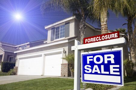 dispossession: Blue Foreclosure For Sale Real Estate Sign in Front of House with Blue Starburst in Sky. Stock Photo