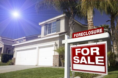dispossession: Red Foreclosure For Sale Real Estate Sign in Front of House with Blue Starburst in Sky.