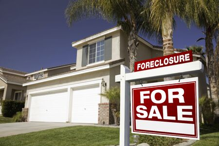 repossession: Red Foreclosure For Sale Real Estate Sign in Front of House.
