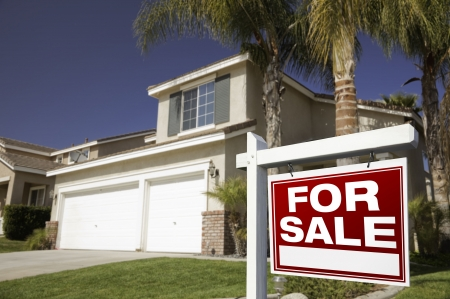 Red For Sale Real Estate Sign in Front of House. Stock Photo