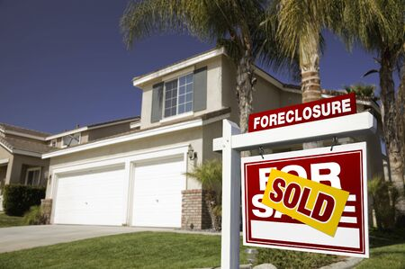Red Foreclosure For Sale Real Estate Sign in Front of House. photo