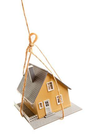 House Hanging by a String Isolated on a White Background. photo