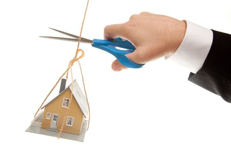 scissors: Hand with Scissors Cutting String Holding House Isolated on a White Background.