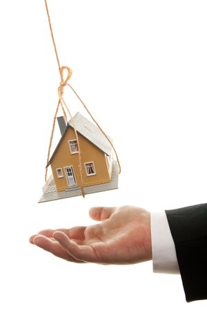 dangling: Businessmans Hand Under Dangling House Isolated on a White Background.