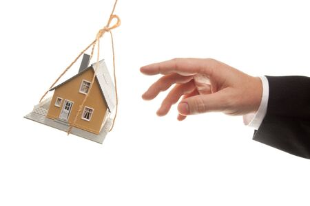 downpayment: Swinging House and Business Mans Hand Reaching or Pushing Isolated on a White Background.