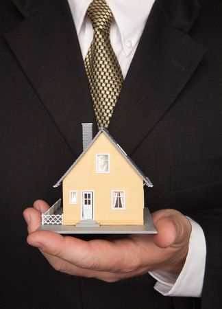 Businessman with Coat and Tie Holding House. photo