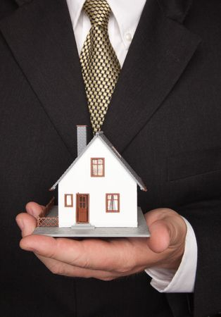 Businessman with Coat and Tie Holding House. Stock Photo - 4675147