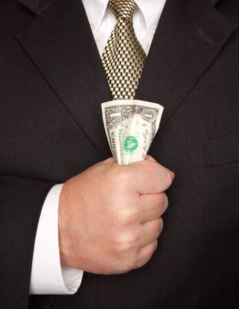 Businessman with Coat and Tie Squeezing Dollar Bill. photo
