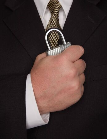 Businessman with Coat and Tie Holding Large Lock. photo