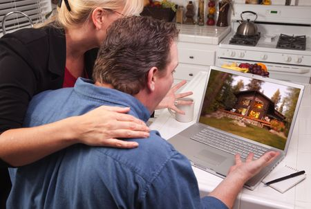 Couple In Kitchen Using Laptop with Lake Cabin on the Screen. photo