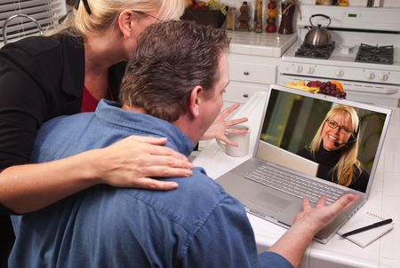Couple In Kitchen Using Laptop with Customer Support Woman on the Screen. photo