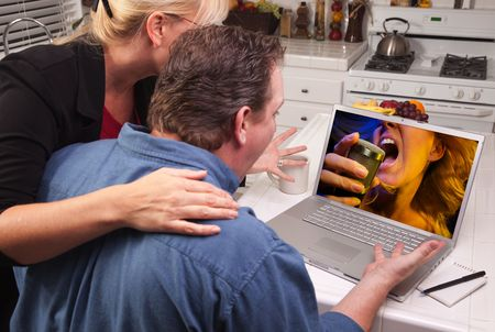 Couple In Kitchen Using Laptop with Singing Woman on the Screen. photo