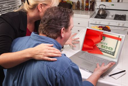 Couple In Kitchen Using Laptop with Stack of Money Wrapped in a Red Ribbon on the Screen. photo
