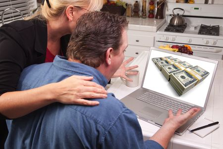 Couple In Kitchen Using Laptop with Stacks of Money on the Screen. photo