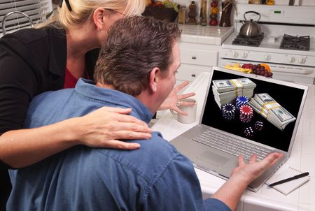 Couple In Kitchen Using Laptop with Stacks of Money and Poker Chips on the Screen. Stock Photo - 4788435