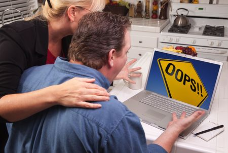 Couple In Kitchen Using Laptop with Yellow Oops Road Sign on the Screen. photo