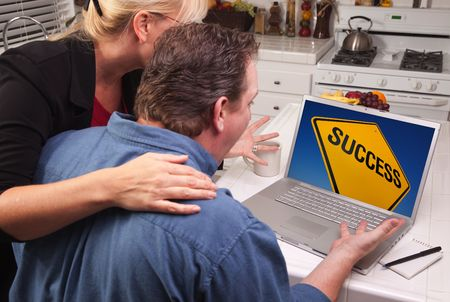 Couple In Kitchen Using Laptop with Yellow Success Road Sign on the Screen. photo