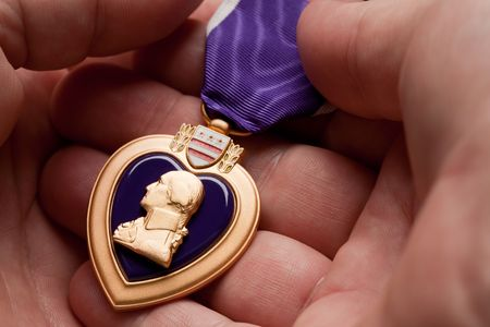 Man Holding Purple Heart War Medal in The Palm of His Hand. photo