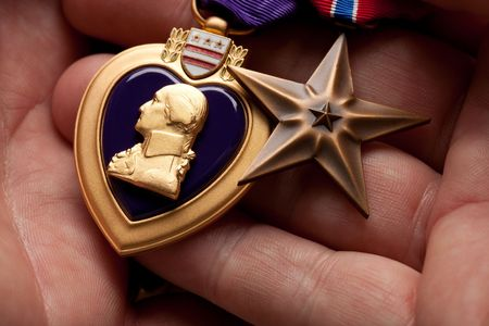 valor: Man Holding Purple Heart and Bronze War Medals in The Palm of His Hand. Stock Photo